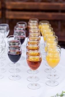 Стеклянные бокалы для вина, наполненные напитками, стоят рядами