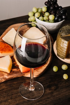 Glass of wine near grapes and cheese