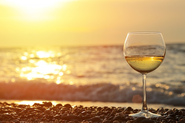 Glass of wine sitting on the beach at colorful sunset glasses of white wine against sunset