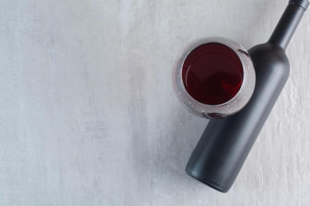 Un bicchiere di vino con bottiglia su sfondo bianco. foto di alta qualità