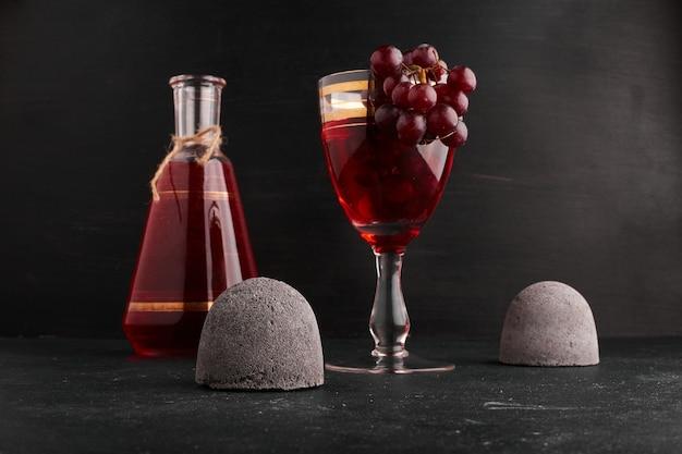 Un bicchiere di vino con un grappolo d'uva.