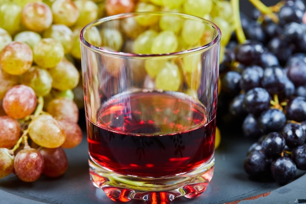 A glass of wine with a bunch of green grapes.