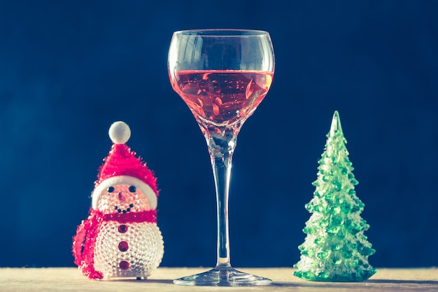 Glass of wine with christmas decorations on the wooden table, black background