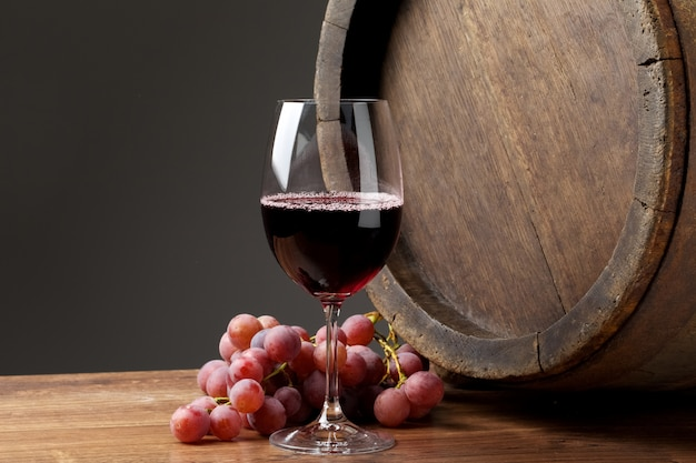 Glass of wine with grapes on wooden table