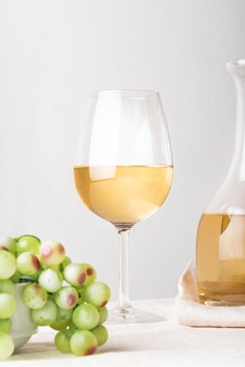 Glass of wine with green grapes close-up