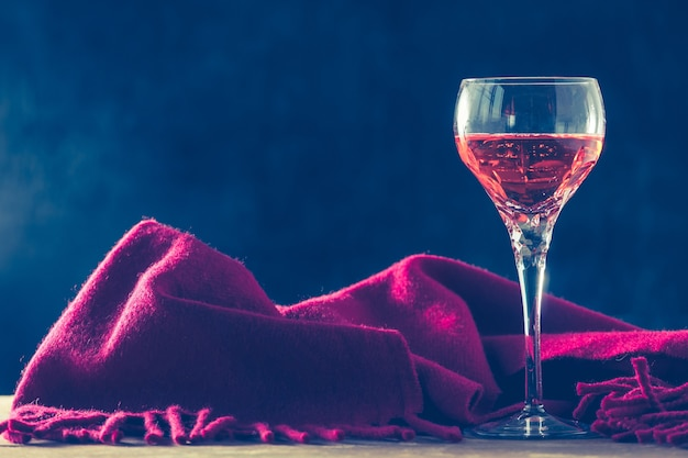 Glass of wine with red scarf on the table, black background