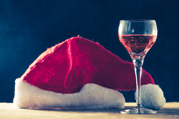 Glass of wine with santa hat on the wooden table, black background.