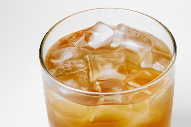 흰색 배경 알코올에 얼음을 넣은 어두운 색 음료가 있는 유리