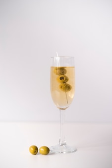 Glass with alcohol and olives over white backdrop
