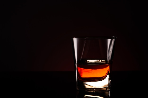 Glass with alcoholic drink on a glass surface