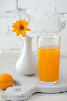 キッチンボードにアプリコットジュースとガラス、白いレンガの壁を背景に木製のテーブルに黄色い花と花瓶。セレクティブフォーカス。閉じる。