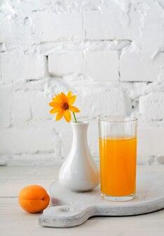 キッチンボードにアプリコットジュースが入ったガラスと、テキスト用のコピースペースがある白いレンガの壁を背景にした木製のテーブルに黄色い花が付いた花瓶。セレクティブフォーカス。閉じる。
