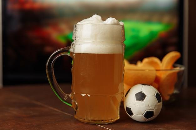 サッカーゲームのサッカーファンと画面の前にビールと軽食とグラス