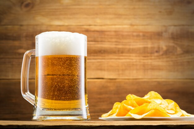 Glass with beer and chips on wooden wall.