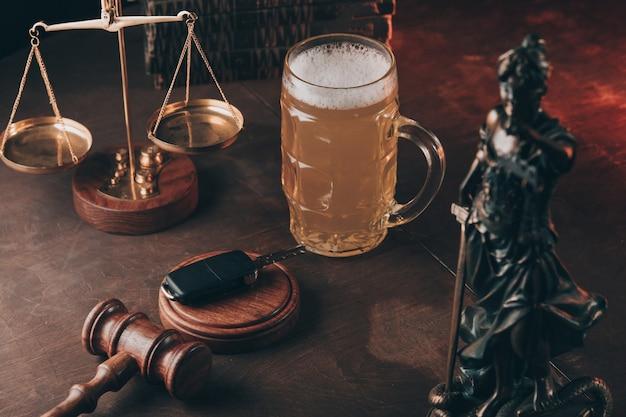 ビールの入ったグラス、正義の女神、木の小槌。