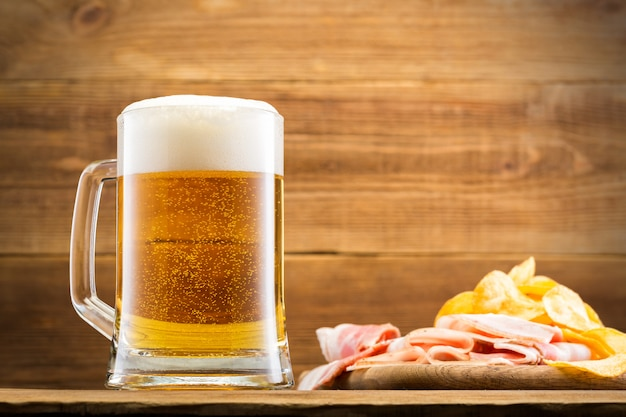 Glass with beer on wooden wall.