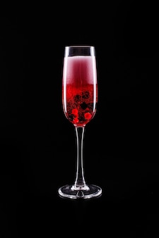 Glass with berries and red champagne alcohol cocktail stands on black background