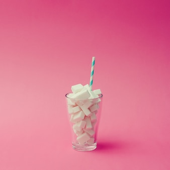 Glass with blue straw filled with sugar cubes on pink surface