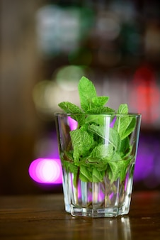 A glass with branches of aromatic mint is on wooden table in the cafe.
