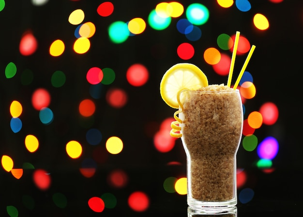 Glass with brown granulated sugar on dark bokeh background