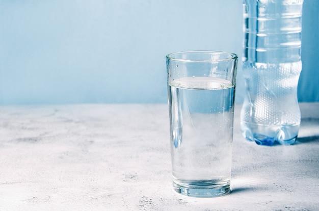 きれいな水とバックグラウンドでペットボトルとガラス