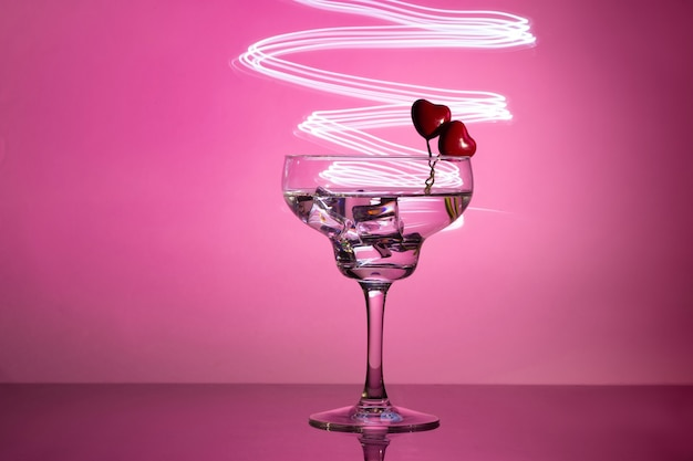 Glass with a cocktail and two hearts. valentine's day and wedding concept.