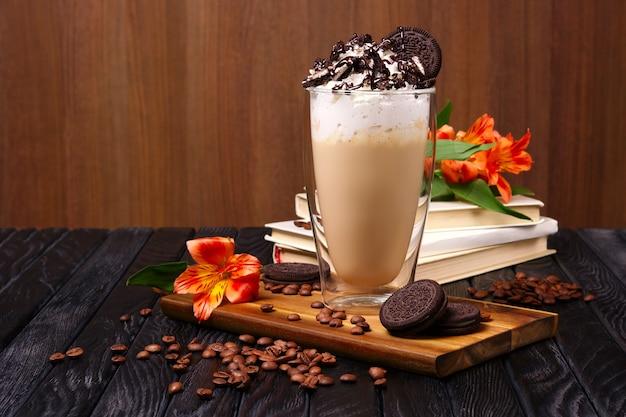 Стакан с кофейным коктейлем со взбитыми сливками и печеньем, украшенный кофейными зернами и цветами