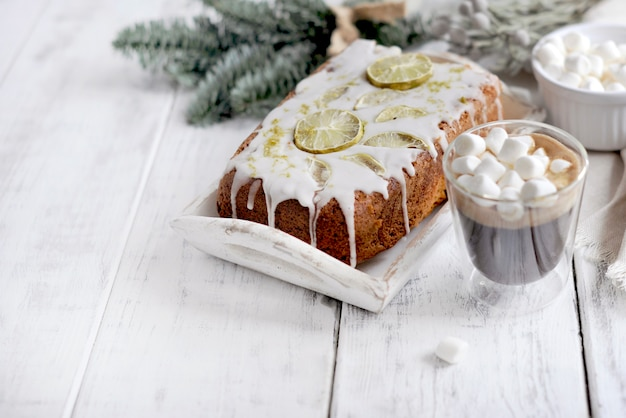 Glass with coffee and small marshmallows, lemon cake and christmas tree branch