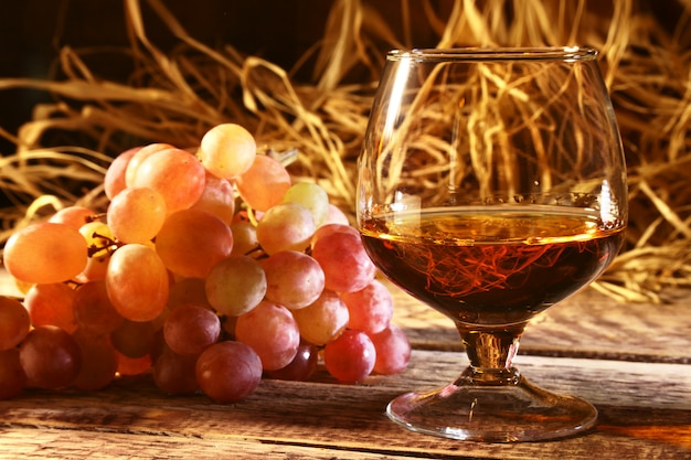 Glass with cognac or brandy and fresh grapes.