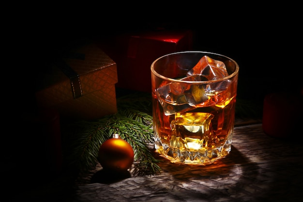 Glass with cognac or whiskey, christmas balls and candles.