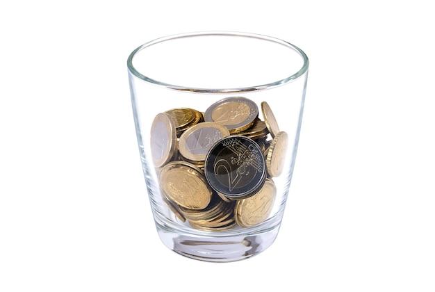 Стакан с монетами на белом фоне