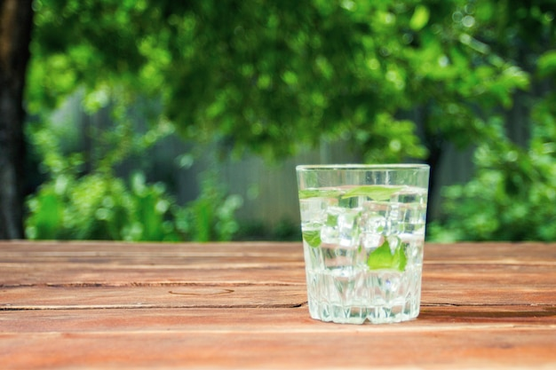 A glass with a cold refreshing drink with ice and mint leaves on a wooden table and in the background of the garden. concept of outdoor recreation