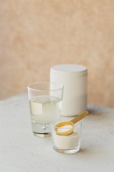 ライトベージュのテーブルにコラーゲンを水に溶かしたガラスとコラーゲンプロテインパウダー。健康的なライフスタイルのコンセプト。