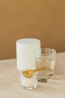 ライトベージュのテーブルにコラーゲンを水に溶かしたガラスとコラーゲンプロテインパウダー。