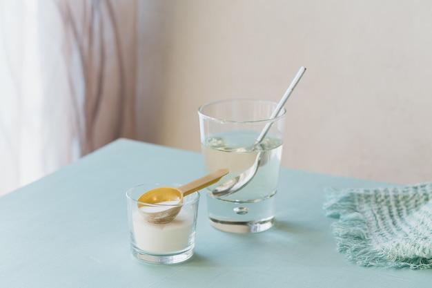 水に溶解したコラーゲンと水色のテーブル上のコラーゲンタンパク質粉末を含むガラス。