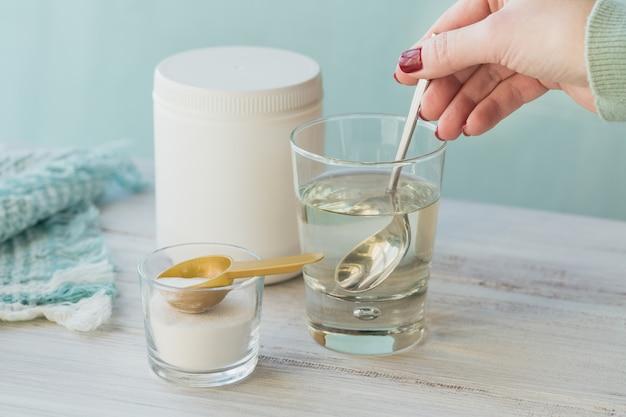 白い木製のテーブルの上に水に溶解したコラーゲンとコラーゲンタンパク質粉末を含むガラス。