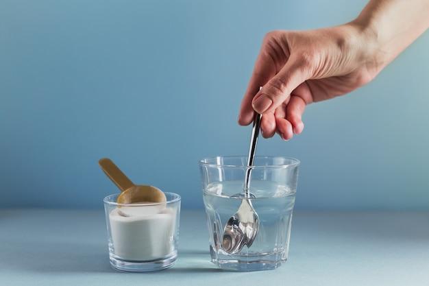 물에 콜라겐이 녹아있는 유리와 하늘색 표면에 콜라겐 단백질 파우더가 있습니다. 여자의 손에 숟가락을 보유하고있다. 건강한 라이프 스타일 개념.