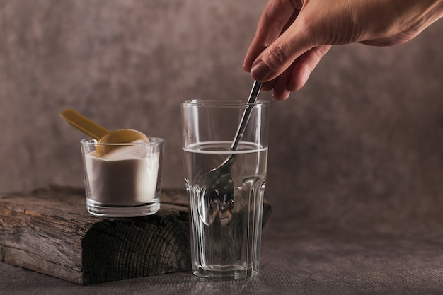 Glass with collagen dissolved in water and collagen protein powder. woman's hand holds a spoon. healthy lifestyle concept.