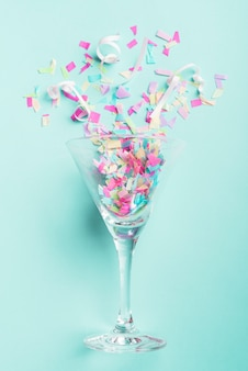 Glass with confetti on turquoise background