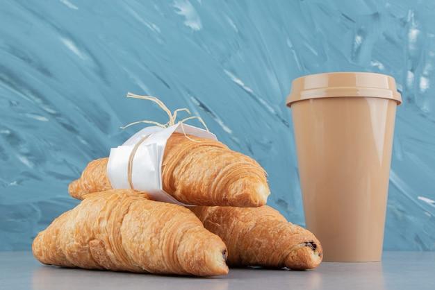 Vetro con croissant sullo sfondo di marmo. foto di alta qualità