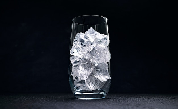 Glass with crushed ice on black background