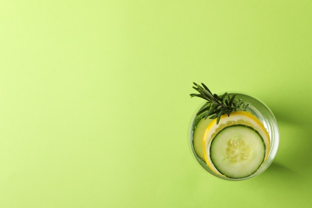 Glass with cucumber water on green surface