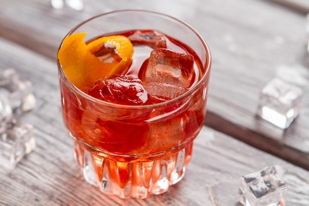 濃いオレンジ色の飲み物とグラス。レモンの皮と角氷。ネグローニカクテルの準備ができました。ビターズ飲料のレシピ。