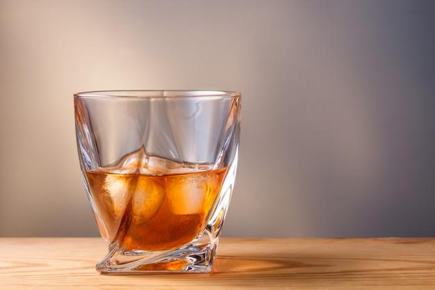 Стакан с напитком и льдом на деревянный стол
