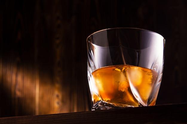 Стакан с напитком и льдом на деревянной стене