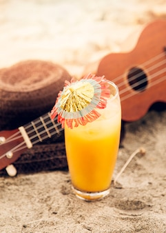 Glass with drink, ukulele and straw hat placed on sand