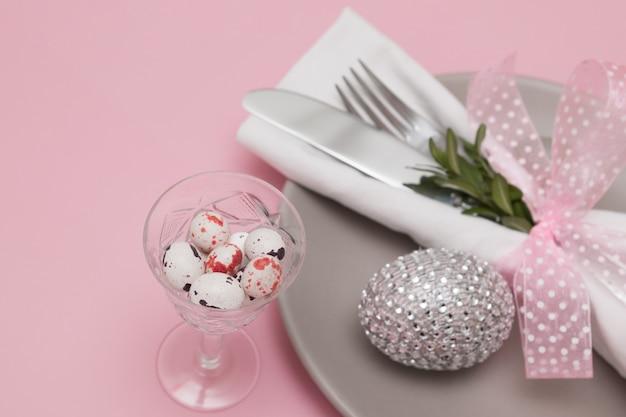 Стекло с пасхальными яйцами на фоне тарелок и столовых приборов. вариативный фокус