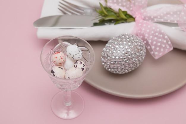 Стакан с пасхальными яйцами на фоне тарелок и столовых приборов