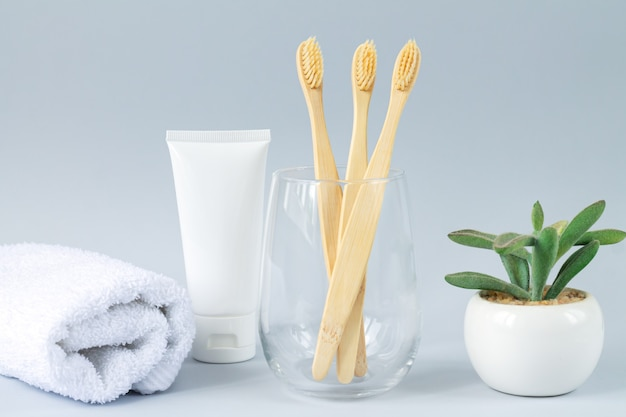 Glass with family set of eco biodegradable bamboo toothbrashes next to toothpaste, towel and green plant