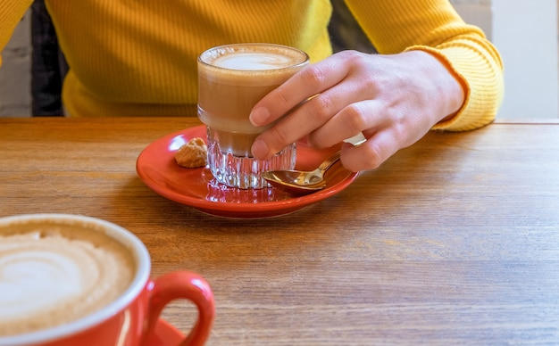 A glass with flat white is held by the hand of young woman in yellow sweater.
